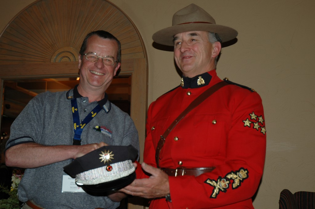 Horst Gennert presents an officer's hat of the Hamburg-Police to an RCMP officer in Calgary. The hat was provided by the Hamburg-Police public-realtions office. (Photo by Thorsten Ehrenberg)